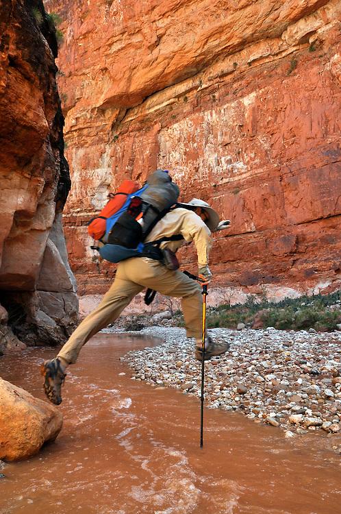 Backpacker leaping across Kanab Creek, Kanab Creek Wilderness, Arizona.