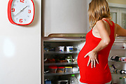 Craving pregnant woman looks for food in the fridge
