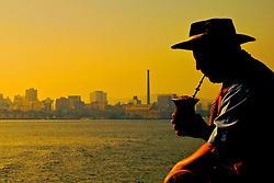 Gaúcho toma chimarão no fimnal do dia com a vista da Usina do gaômetro ao fundo. FOTO: