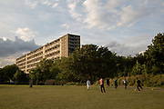 A group of young men playing football in Burgess Park overlooking the Aylesbury Estate, a large housing estate located in Walworth, on 5th August 2016 in South London, United Kingdom.  The Aylesbury Estate contains 2,704 dwellings and was built between 1963 and 1977. The estate is partially occupied and is currently undergoing a major redevelopment.