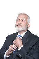 caucasian senior businessman portrait adjusting necktie isolated studio on white background