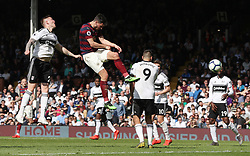 Newcastle United's Fabian Schar (centre left) heads in his side's third goal during the Premier League match at Craven Cottage, London.