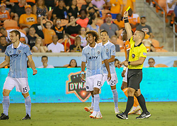 August 4, 2018 - Houston, TX, U.S. - HOUSTON, TX - AUGUST 04:  Referee Chris Penso isses a yellow card to Sporting Kansas City defender Seth Sinovic (15) during the soccer match between Sporting Kansas City and Houston Dynamo on August 4, 2018 at BBVA Compass Stadium in Houston, Texas.  (Photo by Leslie Plaza Johnson/Icon Sportswire) (Credit Image: © Leslie Plaza Johnson/Icon SMI via ZUMA Press)