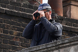 © Licensed to London News Pictures.10/04/2017.London, UK. Police officers use binoculars from a rooftop near Southwark Cathedral in London where the funeral of policeman Keith Palmer is due to take place this afternoon (Mon). PC Palmer was murdered just inside the gate by Westminster attacker Khalid Masood - an attack in which he also killed four people on Westminster Bridge.Photo credit: Tom Nicholson/LNP