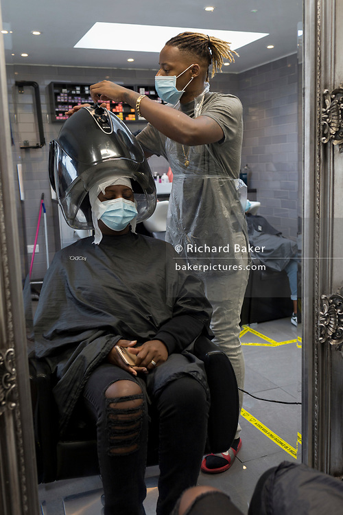 As the UK eases further from Coronavirus pandemic restrictions - a relaxation of rules such as 'one metre plus' distance rule and the re-opening of pubs, bars, restaurants and hairdressers - staff and customers at the Carl Campbell hairdressers get used to social distancing and the wearing of PPE (personal protection equipment) face coverings in the salon, on Coldharbour Lane in Brixton, on 4th July 2020, in London, England. Under current in hair salons rules, to prevent the spread of airbourne droplets, conversation is meant to be kept to a minimum but the wearing by customers of face coverings is not actually mandatory.