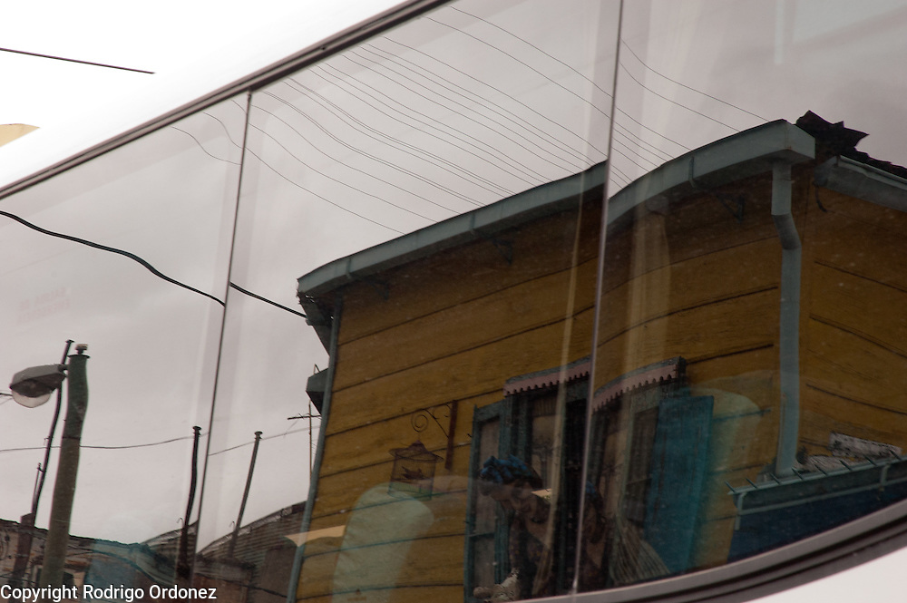 A bus window reflects the view of Caminito street, in La Boca neighborhood of Buenos Aires, Argentina.<br /> Caminito is a pedestrian street created in the late 1950s by local painter Benito Quinquela Martín and other artist friends to recreate a version of the old immigrant neighborhood of La Boca, using wood and corrugated zinc painted in bright colors. Today, Caminito and the surrounding areas feature cafes, souvenir shops, tango dancers and other street performances aimed to attract tourists.