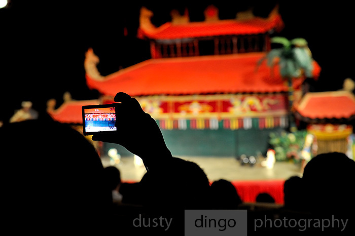 A member of the audience takes a photograph of a traditional Vietnamese Water Puppet (Mua Roi Nuoc) performance in Ho Chi Minh City (Saigon), Viet Nam