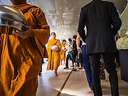 """29 NOVEMBER 2016 - BANGKOK, THAILAND:  Buddhist monks walk through the skywalk after collecting alms from people during a special """"tak bat"""" or merit making ceremony in the Ratchaprasong skywalk of the Bangkok BTS system. The tak bat was to honor Bhumibol Adulyadej, the Late King of Thailand. Food and other goods were given to the monks, who in turn gave the items to charities that will distribute them to Bangkok's poor. More than 100 Buddhist monks participated in the merit making ceremony. The ceremony was organized by the merchants in the Ratchaprasong Intersection, which includes some of Bangkok's most upscale shopping centers.     PHOTO BY JACK KURTZ"""
