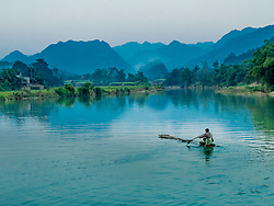 Asia, Vietnam, Pu Luong Nature Reserve, man paddling bamboo raft on the Cham River.