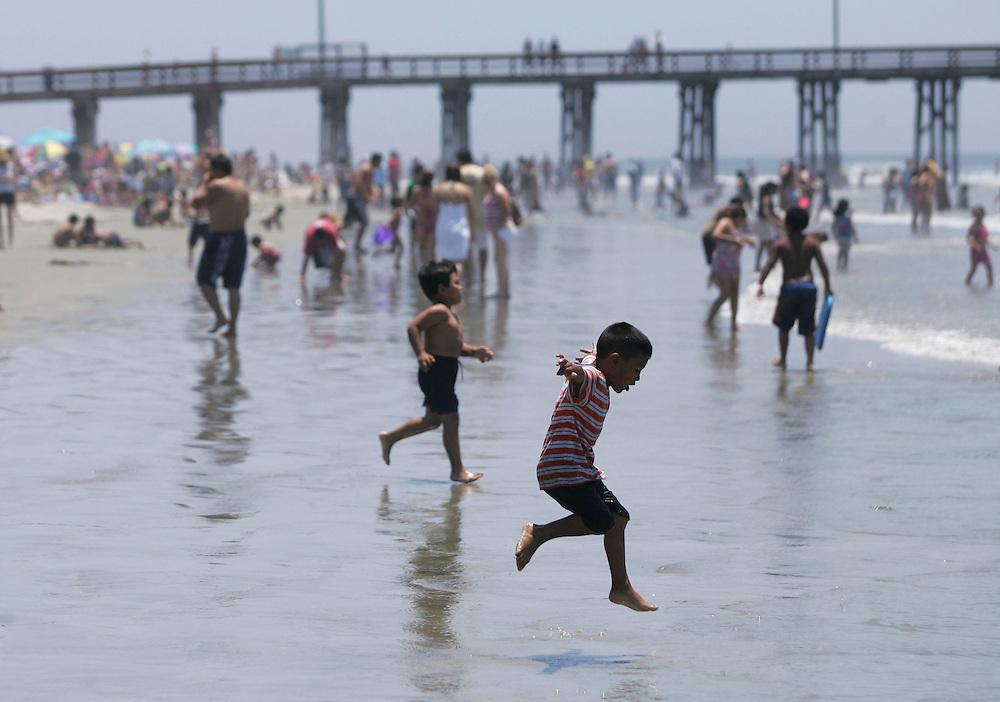 Children play near the pier in Newport Beach Saturday July 1, 2006.