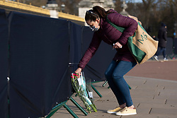 **Caption correction - Pictures taken today 11/04/2021**<br /> © Licensed to London News Pictures.11/04/2021. London, UK.A woman places a note on flowers outside Buckingham Palace. On Friday the 9th of April Buckingham Palace announced that Prince Philip The Duke of Edinburgh passed away in the morning at Windsor Castle . Photo credit: George Cracknell Wright/LNP