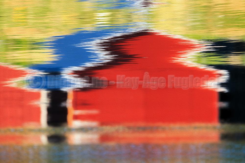 Mirrored reflection of a boathous in the sea | En speilvendt speiling i sjøen av et naust