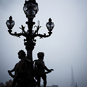 An ornate lamp post with statues is silhouetted on a very rainy and overcast day in Paris, with the Eiffel Tower in the distance.