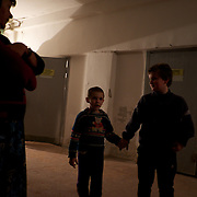DONETSK, UKRAINE - OCTOBER 20, 2014: Two young children are seen at a improvised bomb shelter in the basement of an old typography in Kievskiy district. Valentina moved to the shelter together with her daughter, around four months ago, after getting her house partially destroyed during fighting between DNR separatist combatants and the Ukrainian National Guard. CREDIT: Paulo Nunes dos Santos