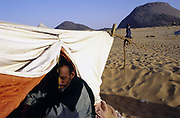 A nomad in his tent in the Sahara Desert between the cities of Chinguetti and Choum in Mauritania. Nomads live by trading their camels and produce that they buy and sell. Behind the tent is Ben Amera, the world's second largest monolith.