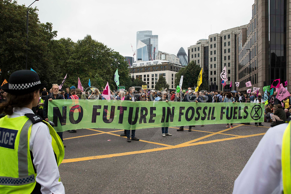 Environmental activists from Extinction Rebellion block the Tower Gateway one-way system during an Impossible Tea Party event on 30th August 2021 in London, United Kingdom. Extinction Rebellion were drawing attention to financial institutions funding fossil fuel projects whilst calling on the UK government to cease all new fossil fuel investment with immediate effect on the eighth day of their Impossible Rebellion protests in London.