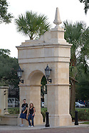 Pedestrians walk past the stone entrance to Rollins College in Winter Park, Florida.