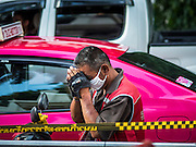 18 AUGUST 2015 - BANGKOK, THAILAND: A motorcycle taxi driver in Bangkok bows his head in prayer while he waits in front of Erawan Shrine, which was damaged by a bomb Monday night. An explosion at Erawan Shrine, a popular tourist attraction and important religious shrine in the heart of the Bangkok shopping district, killed at least 20 people and injured more than 120 others, including foreign tourists, during the Monday evening rush hour. Twelve of the dead were killed at the scene. Thai police said an Improvised Explosive Device (IED) was detonated at 18.55. Police said the bomb was made of more than six pounds of explosives stuffed in a pipe and wrapped with white cloth. Its destructive radius was estimated at 100 meters.    PHOTO BY JACK KURTZ