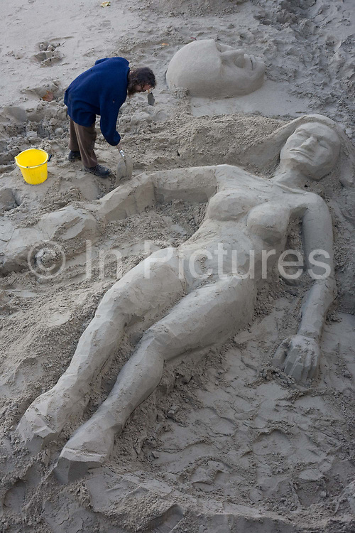 A sculptor shapes the female form of an oversized woman sunbather  made from sand on the Thames foreshore on London's South Bank. Working with great care and patience  the artist who is a well-known character on this stretch of low-tide beach uses a yellow bucket and a wide shovel to dig  then work the soft sand into this shape of a giant reclining female who apparently wears a bikini and a hat or some kind. Come the changing tide however  his showcase will disappear beneath the capital's river waters that will soon lap against the south bank riverside at Gabriel's Wharf.