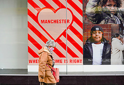 © Licensed to London News Pictures. 26//11/2020. Manchester, UK. A shopper wearing a face mask walks in Manchester city centre. Manchester will face very tough measures to contain the spread of the Coronavirus as moved into Tier 3 from 2 December. Photo credit: Ioannis Alexopoulos/LNP