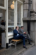 Two businessmen take coffee while checking messages outside a cafe on Threadneedle Street in the City of London, the capital's financial district, on 3rd May 2019, in London, England