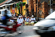 A pemangku (local priest) carrying out a Hindu ceremony at a crossroad with traffic all around. Sanur, Bali, Indonesia.