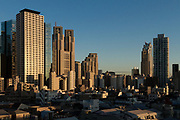 The towers of the Tokyo Metropolitan Government Buildings among other skyscrapers, and low-rise houses Shinjuku, Tokyo, Japan. Tuesday November 29th 2016