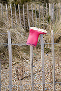 Lost red child's wellington boot on fence post, Dunwich, Suffolk, England