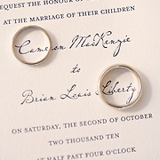 A fun way to photograph wedding bands and invitations by encircling the Bride's first name and new last name with a ring.