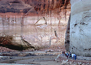 Visitors to the Rainbow Arch on Lake Powell walk a trail from their boat to the the formation.  An ongoing drought has reduced the water level in the lake making the hike much farther than in previous years.