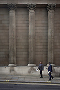 Men of African appearance walk smiling beneath the tall pillars of Britain's monetary establishment, the Bank of England