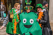People in many types of green hats and other costumes are well wrapped up against the cold as they watch the parade go by -  the London St Patrick's Day parade from Piccadilly to Trafalgar Square.