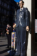 Scale model of world's tallest man Robert Pershing Wadlow in London street with similar-looking man eating junk food.<br /> <br /> Robert Pershing Wadlow (February 22, 1918 – July 15, 1940) is the tallest person in history. He reached 8 ft 11.1 in (2.72 m)[2][3] in height and weighed 485 lb (220 kg) at his death at age 22. His great size and his continued growth in adulthood was due to hypertrophy of his pituitary gland which results in an abnormally high level of human growth hormone. He showed no indication of an end to his growth even at the time of his death.