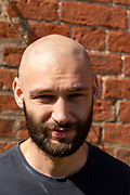 Full face portrait close up Caucasian white young man shaven head and beard