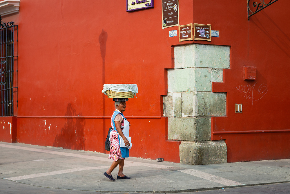 Street vendor carrying a basket on her head in Oaxaca, Mexico