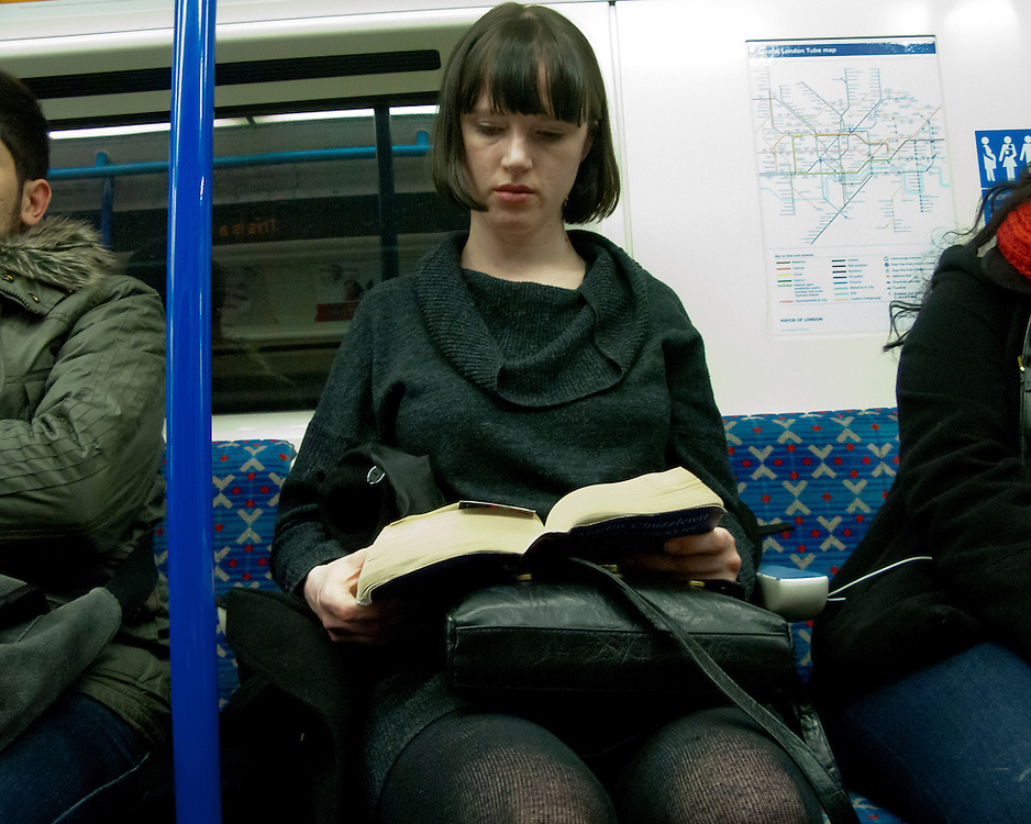 Woman reading a book on the London Underground Network