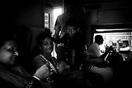 Sri Lankan adults and children travel by train between the cities of Colombo and Kandy in Sri Lanka.