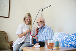 Senior man with stethoscope listening at the heartbeat of his doctor, Bavaria, Germany, Europe