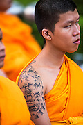 20 OCTOBER 2012 - BANGKOK, THAILAND:  A Buddhist monk with a Hanuman tattoo on his shoulder at an alms giving ceremony in Bangkok. More than 2,600 Buddhist Monks from across Bangkok and thousands of devout Thai Buddhists attended the mass alms giving ceremony in Benjasiri Park in Bangkok Saturday morning. The ceremony was to raise food and cash donations for Buddhist temples in Thailand's violence plagued southern provinces. Because of an ongoing long running insurgency by Muslim separatists many Buddhist monks in Pattani, Narathiwat and Yala, Thailand's three Muslim majority provinces, can't leave their temples without military escorts. Monks have been targeted by Muslim extremists because, in the view of the extremists, they represent the Thai state.       PHOTO BY JACK KURTZ