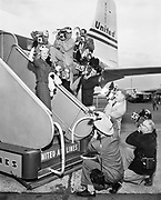 delay540607A-3. Oregon Press Photographers. Donna Lee Johnson, Miss Oregon Press Photographer, at airport. June 7, 1954. See description for OPS_08-10. Photographers left to right; unidentified; Rollie Dobson, Oregonian; (below) Don Johnson, NW Natural Gas; (above) unidentifed; (face behind strobe) Dick Farris, Oregonian; Dave Falconer, Oregonian; Dean Bond, Pacific NW Bell; (below) Al Monner, Oregon Journal; Chet Buchtel, City of Portland.