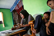 Habiba Binti Ketui left - a smallholder palm oil farmer does her paperwork next to her grandsons in their home in Beluran District, Sabah, Malaysia, on 9 September 2016. Habiba has been farming her small plot since the late 1990s. She has been able to increase her yields since becoming part of the Wild Asia Group scheme, which works with the Roundtable on Sustainable Palm Oil to support Malaysian smallholders to become certified sustaianble. This includes improving farm management, reducing their use of pesticides and fertilizers, and increasing yields.