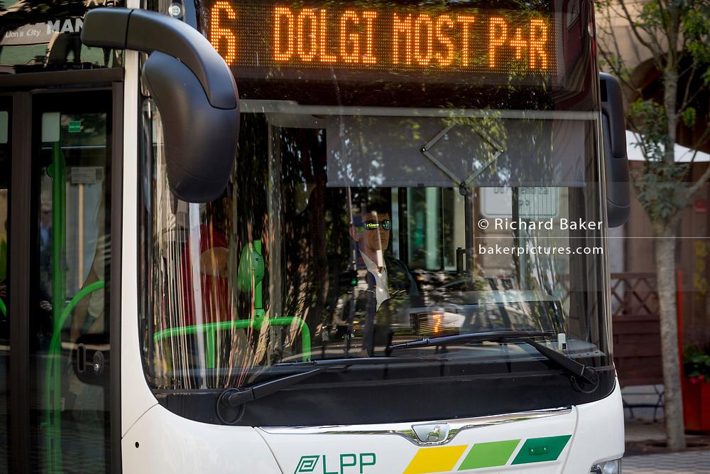 A bus driver seen through the front of a city bus on Slovenska Cesta (street) in the Slovenian capital, Ljubljana, on 25th June 2018, in Ljubljana, Slovenia. Ljubljana city buses are operated by the Ljubljanski potniški promet (LPP) public utility company.