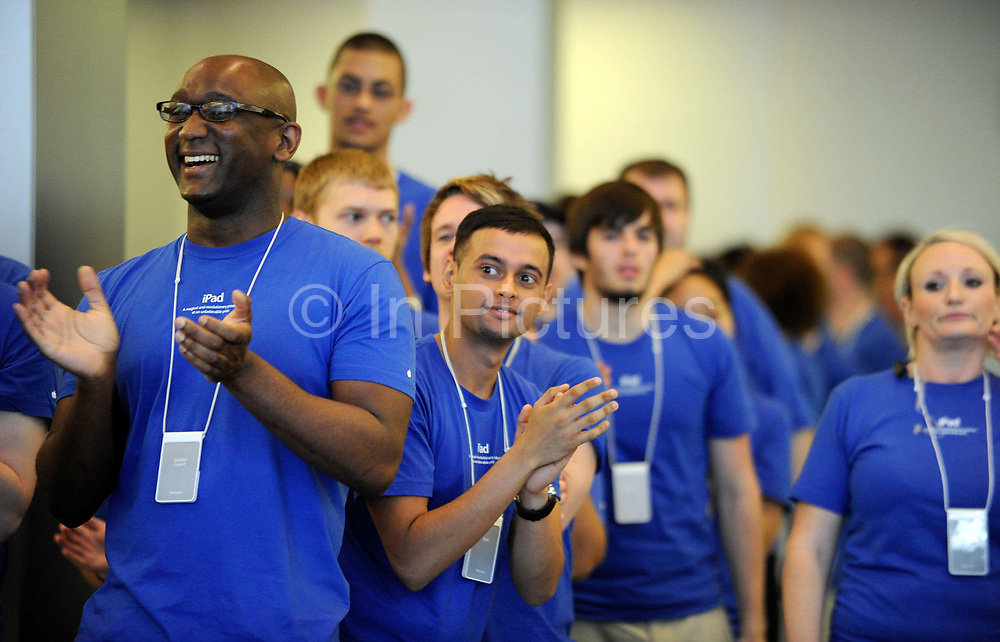 Staff at the Apple store cheer as customers begin to arrive for the new iphone 4 at the Apple store in central London.