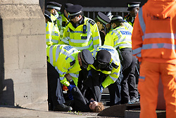 © Licensed to London News Pictures. 04/10/2021. London, UK. Police attempt to remove an activist from Insulate Britain at the entrance to the Blackwall tunnel after the group blocked the tunnel earlier this morning. Insulate Britain have successfully blocked various roads around the capital over a number of weeks, resulting in a court injunction banning them from going near the M25 motorway.  Photo credit: George Cracknell Wright/LNP