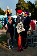 """Damaged airhostess's in Unfairground. One carrying a cotton shoulder bag with the words """"Stop using carrier bags"""", Glastonbury Festival 2010"""