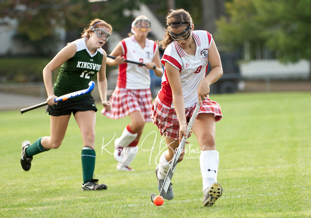 Laconia's Beth Kneuer storms past Kingswood's Brittany Drapeau to score the first of two goals for Laconia during Tuesday's Division II field hockey game played at Opechee Park.    (Karen Bobotas/for the Laconia Daily Sun)