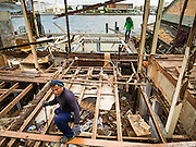 12 NOVEMBER 2015 - BANGKOK, THAILAND:  Demolition workers tear down a home at Wat Kalayanmit. Fifty-four homes around Wat Kalayanamit, a historic Buddhist temple on the Chao Phraya River in the Thonburi section of Bangkok, are being razed and the residents evicted to make way for new development at the temple. The abbot of the temple said he was evicting the residents, who have lived on the temple grounds for generations, because their homes are unsafe and because he wants to improve the temple grounds. The evictions are a part of a Bangkok trend, especially along the Chao Phraya River and BTS light rail lines. Low income people are being evicted from their long time homes to make way for urban renewal.       PHOTO BY JACK KURTZ