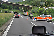 Italie, 15-5-2019 Lange rijen autos en wachten voor de ingang van de Gotthardtunnel op groen licht voor de doorgang. Er heeft zich een ongeluk voorgedaan bij de ingang van de tunnel en een auto is in brand gevlogen . Vanwege de veiligheid mag er slechts gedoseerd verkeer doorheen, en moet lang gewacht worden. Deze weg is de toegang tot Italie . Foto: ANP/ Hollandse Hoogte/ Flip Franssen