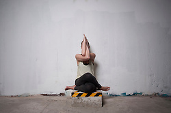 Mid adult woman practicing cow face pose in yoga studio, Munich, Bavaria, Germany