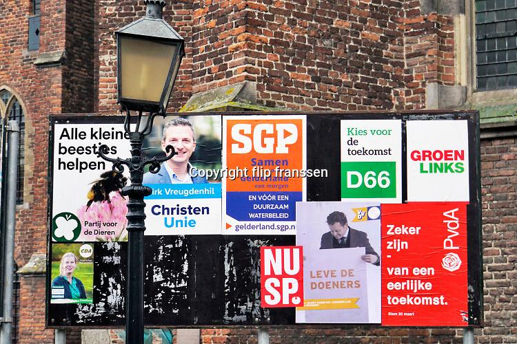 Nederland, Doesburg, 9-3-2019 Verkiezingsbord in de binnenstad waarop affiches voor de komende provinciale verkiezingen zijn aangebracht. Op het bord is het PvdA affiche afgescheurd door iemand met ondemocratische gedachten . Partij van de Arbeid . Foto: Flip Franssen